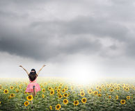 Happy woman jump in sunflower fields and rainclouds Stock Images
