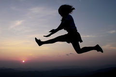 A happy woman jump at the sunset Stock Image