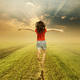 Happy woman jump on way of green grass and sunset Stock Image