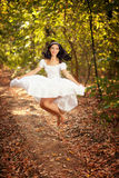 Happy woman jumping. Beautiful happy brunette woman in vintage white dress jumping in the forest Royalty Free Stock Photo