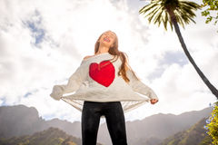 Happy woman jumping against the sky. Young woman in the sweater with heart shape jumping against the sky expressing happiness and freedom Stock Photo