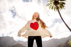 Happy woman jumping against the sky. Young woman in the sweater with heart shape jumping against the sky expressing happiness and freedom Royalty Free Stock Photography
