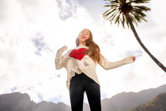 Happy woman jumping against the sky. Young woman in the sweater with heart shape jumping against the sky expressing happiness and freedom Stock Images
