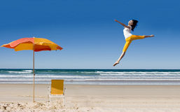 Happy woman jumping at beach Stock Image