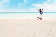 Happy woman jumping on beach Stock Photo