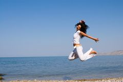 Happy woman is jumping in the beach royalty free stock photo