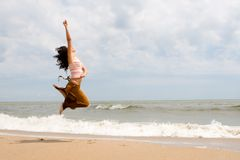Happy woman is jumping in beach Stock Photos