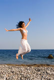Happy woman jumping in the beach Stock Image