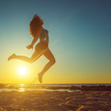 Happy woman jumping on the beach against beautiful yellow sunset Royalty Free Stock Photo