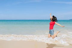 Happy Woman jumping on the beach and clouds  sky Royalty Free Stock Image
