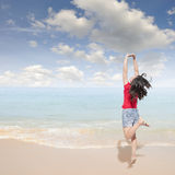 Happy Woman jumping on the beach and clouds  sky Royalty Free Stock Images