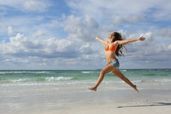 Happy woman jumping on the beach on holidays Royalty Free Stock Images