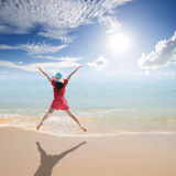 Happy Woman jumping on the beach and sun sky Royalty Free Stock Images
