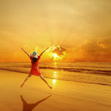 Happy Woman jumping on the beach and sunset Stock Photo