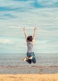 Happy woman jumping on the beach Stock Images
