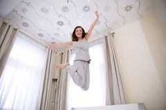 Happy woman jumping on the bed Stock Images