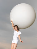 Happy woman jumping with big, white balloon Stock Images