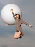 Happy woman jumping with big, white balloon Royalty Free Stock Photo