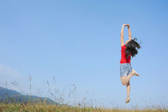 Happy Woman Jumping with blue sky outdoor Stock Photography