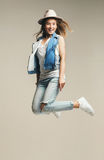 Happy woman jumping in denim waistcoat and hat Royalty Free Stock Photos