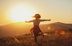 Happy woman jumping and enjoying life  at sunset in mountains Stock Images
