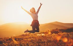 Happy woman jumping and enjoying life at sunset in mountains royalty free stock photo