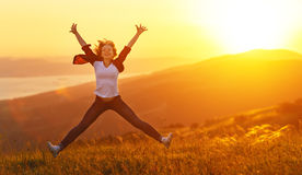 Happy woman jumping and enjoying life  at sunset in mountains Stock Photos