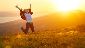 Happy woman jumping and enjoying life  at sunset in mountains Stock Image