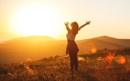 Happy woman jumping and enjoying life at sunset in mountains royalty free stock photography