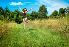 Happy woman jumping in a field Royalty Free Stock Images