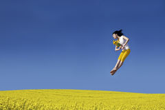 Happy Woman jumping with flower stock photo