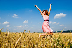 Happy woman jumping in golden field Stock Photo
