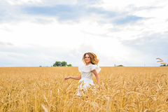 Happy woman jumping in golden wheat Stock Photos