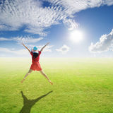 Happy woman jumping in grass fields and blue sky Royalty Free Stock Photo