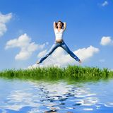 Happy woman jumping in green grass Royalty Free Stock Images