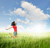 Happy Woman jumping in green grass fields with clouds sky Stock Images