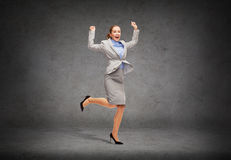 Happy woman jumping with hands up Stock Photos