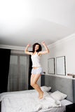 Happy woman jumping on her bed. Royalty Free Stock Photo