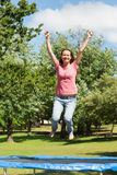 Happy woman jumping high on trampoline in park Stock Photo