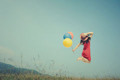 Happy Woman Jumping and holding balloon with blue sky outdoor. vintage tone Stock Image