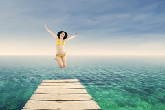 Happy woman jumping on the jetty Stock Photography
