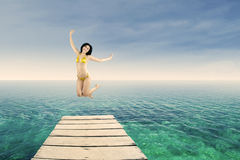 Happy woman jumping on the jetty 1 Stock Images