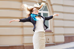 Happy woman jumping for joy in city.  stock image