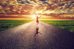 Happy woman jumping on long straight road, way towards sunset sun. Travel, happiness, win, healthy lifestyle concepts stock photography