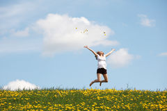 Happy woman jumping on meadow. Stock Photo