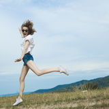 Happy woman jumping on meadow. Royalty Free Stock Image