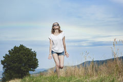 Happy woman jumping on meadow. Royalty Free Stock Images