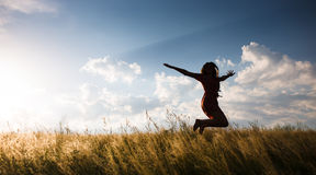 Happy woman jumping in the meadow Royalty Free Stock Image