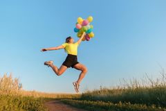 Happy woman jumping with multicolored balloons royalty free stock image