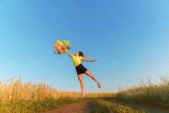Happy woman jumping with multicolored balloons stock photos